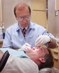 Knoxville Dental Services Dr. Kotsianas conducting a patient's dental exam.