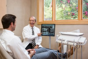 Dr. Kotsianas in his West Knoxville dentist office showing a new patient x-rays. A large window into a garden lines the wall.